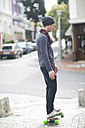 Young man standing on  his skateboard on sidewalk - ZEF000041