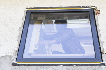 Man with water level at window during house renovation - DRF001089