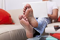 Man sitting barefoot on a couch using laptop at home - JUNF000019