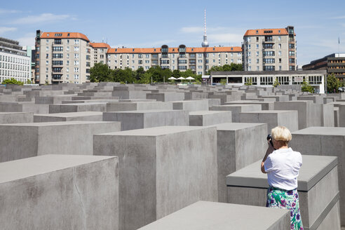 Germany, Berlin, Holocaust Memorial, Mature woman photographing steles - WIF000946