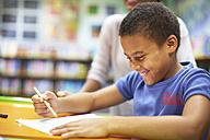Young woman teaching boy writing on paper - ZEF000756