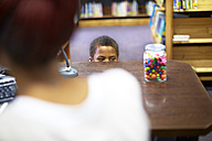 Boy in library peeking at candy jar - ZEF000185