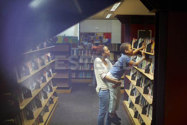 Young woman holding boy at book shelf in library - ZEF000194