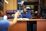 Man and boy throwing paper planes in library - ZEF000762