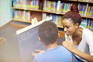 Young woman doing maths with boy in library - ZEF000198