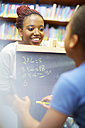 Young woman doing maths with boy in library - ZEF000201