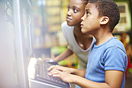 Young woman and boy using computer in library - ZEF000208