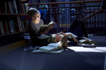 Female student lying on floor in a library with friend reaing book - ZEF000104