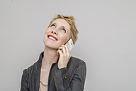 Portrait of smiling blond woman telephoning with smartphone looking up - TCF004233