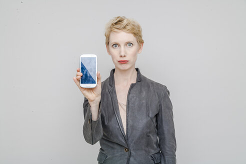 Portrait of unlucky blond woman showing her smartphone in front of grey background - TCF004243