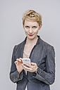 Portrait of blond woman with her smartphone in front of grey background - TCF004247