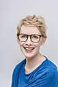 Portrait of smiling blond woman wearing glasses in front of grey background - TCF004264