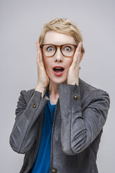 Portrait of frightened blond woman with hands on her face - TCF004266