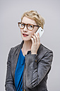 Portrait of smiling blond woman wearing glasses telephoning with smartphone in front of grey background - TCF004274