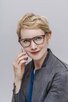 Portrait of smiling blond woman wearing glasses telephoning with smartphone in front of grey background - TCF004275
