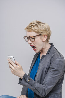 Blond woman looking at her smartphone screaming - TCF004278