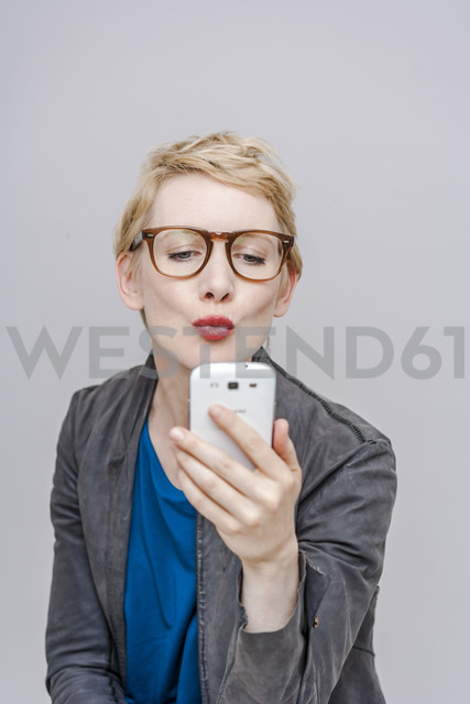 Blond woman pouting mouth taking a selfie with her smartphone - TCF004285