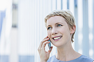 Portrait of smiling blond woman telephoning with smartphone - TCF004316