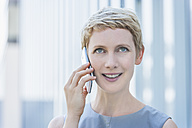 Portrait of smiling blond woman telephoning with smartphone looking up - TCF004318