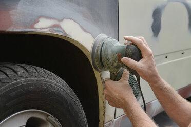 Germany, Zeuthen, Man mending car paint - BFRF000499