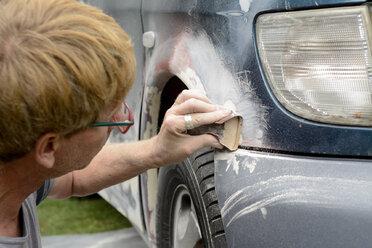 Germany, Zeuthen, Man mending car paint - BFRF000505