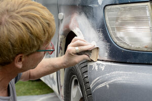 Germany, Zeuthen, Man mending car paint - BFRF000505