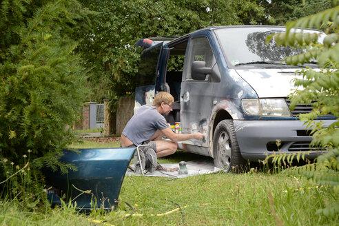 Germany, Zeuthen, Man mending car paint - BFRF000506