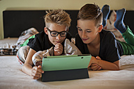 Two boys lying on bed using digital tablet - PAF000861