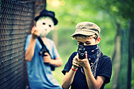 Masked boy aiming with toy gun - PA000850