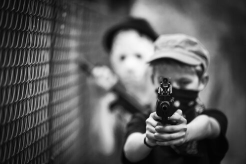 Masked boy aiming with toy gun - PA000852