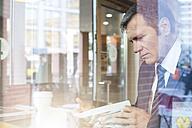 Germany, Berlin, Businessman in coffee shop, taking a break - FKF000620