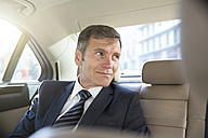 Germany, Berlin, Businessman in taxi - FKF000629
