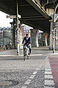Germany, Berlin, Businessman cycling in the city - FKF000637