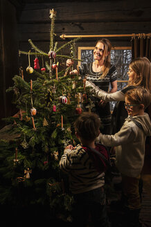 Mother and her three children decorating Christmas tree in a farmhouse - HHF004859