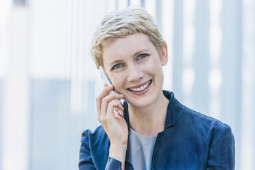 Portrait of smiling blond woman telephoning with smartphone - TCF004440