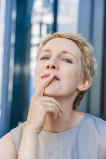 Portrait of blond woman with head back and finger on her mouth - TCF004443