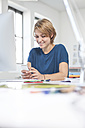 Portrait of smiling young woman using  smartphone at her desk in a creative office - RBF001805