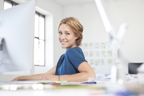 Portrait of smiling young woman at her desk in a creative office - RBF001835
