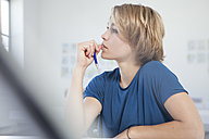Portrait of pensive young woman at her desk in a creative office - RBF001837
