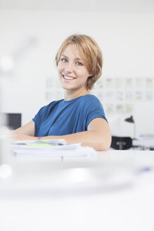 Portrait of smiling young woman at her desk in a creative office - RBF001845