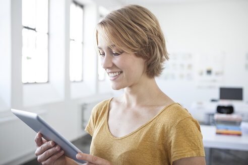 Portrait of smiling young woman with digital tablet in a creative office - RBF001814