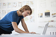 Portrait of young woman using laptop in a creative office - RBF001846
