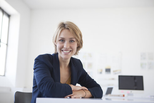 Portrait of smiling young woman at her desk in a creative office - RBF001848