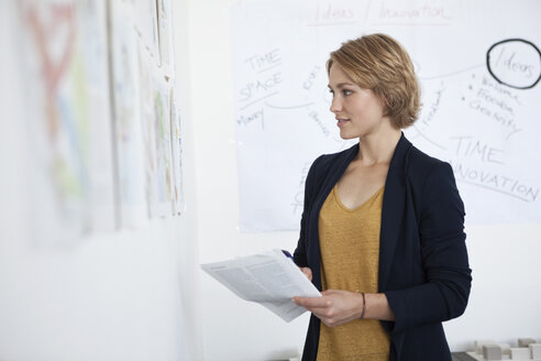 Portrait of young woman looking at a wall with concepts in an office - RBF001851