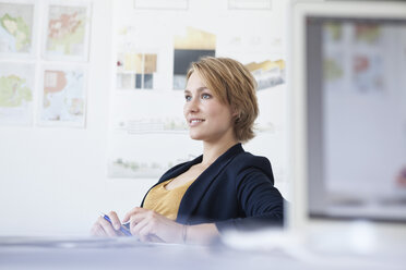 Portrait of smiling young woman at her desk in a creative office - RBF001854