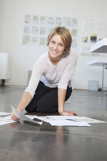 Portrait of young woman sitting on the floor of an office with her concepts - RBF001858