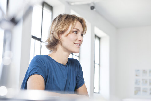 Smiling young woman at her desk in a creative office - RBF001818