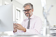 Portrait of smiling man using smartphone at his desk in an office - RBF001824
