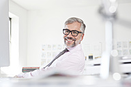 Portrait of smiling man at his desk in an  office - RBF001827