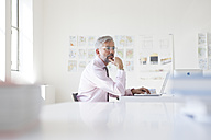 Pensive businessman with laptop at his desk in an office - RBF001885